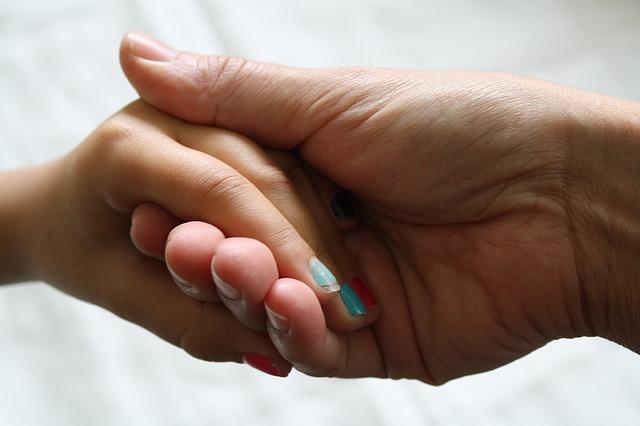 une main d'adulte et une main d'enfant-parents31.fr